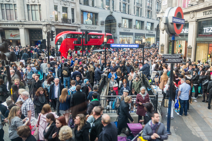Crowded Oxford Circus Station entrance due to severe delays in the tube Central Line. Lots of commuters and tourists waiting on the street to enter the station.